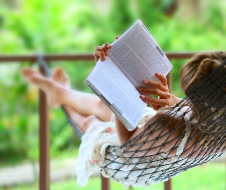 Woman in hammock reading book