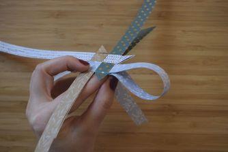 Schritt 22: Das Streifenende wird wieder durch die Lasche gezogen, die oberhalb der entstandenen Zacke liegt.