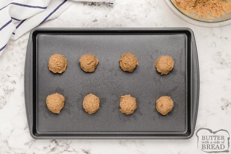 Butterfinger cookie dough balls on a cookie sheet
