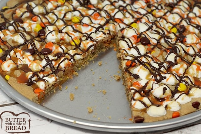 Halloween Peanut Butter Cookie Pizza is topped with marshmallows and Reese's Pieces and then drizzled with chocolate, caramel and orange icing!