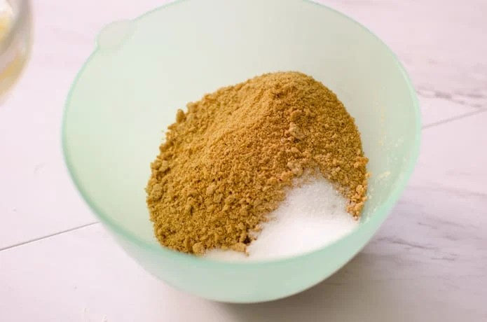 Graham Cracker crumbs and sugar combine with butter to Make the crust.