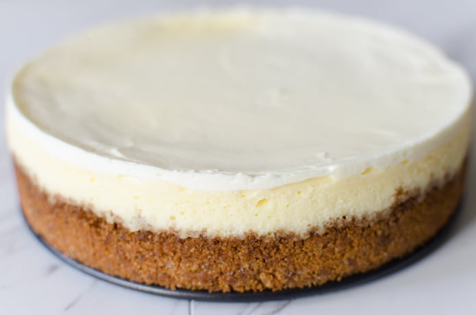 The sour cream layer of this cheesecake is visible in this photo seen as the bright white top layer.