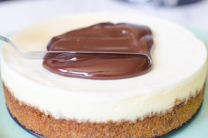 The chocolate ganache is being spread with an offset spatuala onto the cheesecake.