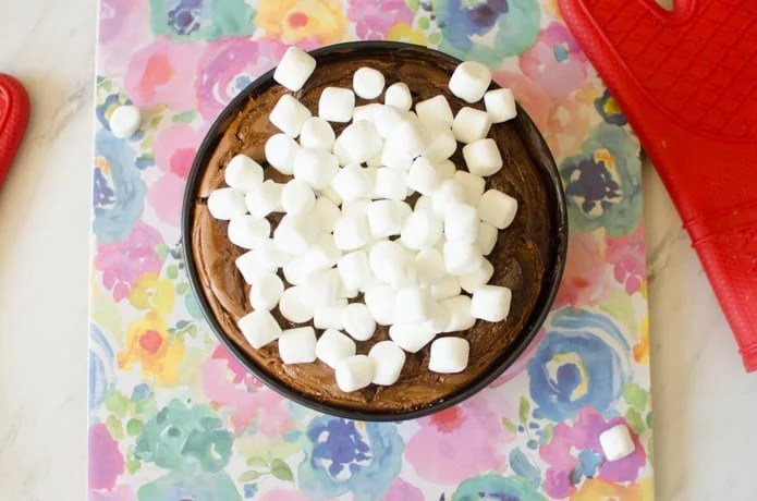 Marshmallows onto of the chocolate cheesecake before being broiled in the oven.