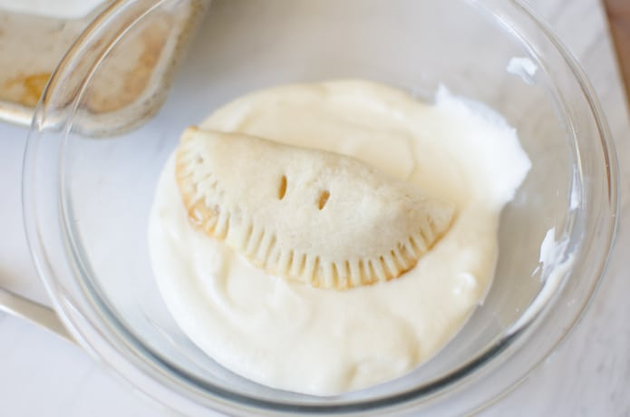 An apple hand pie sitting in vanilla glaze before being covered in the glaze.