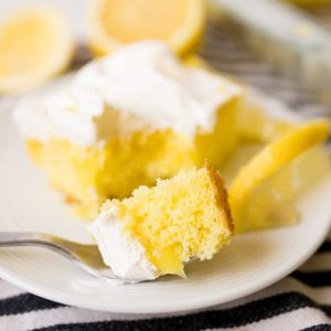 Lemon poke cake with lemon pie filling, plated, with some cake on the fork.