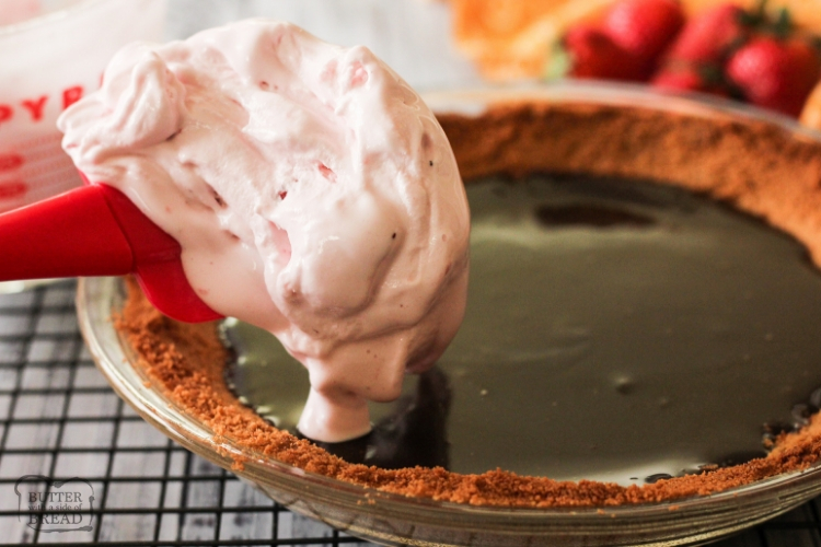 spatula of softened strawberry ice cream over pie pan of hot fudge and graham cracker crust