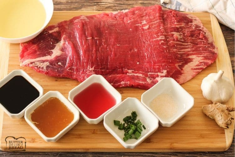 flank steak surrounded by marinade ingredients in white bowls