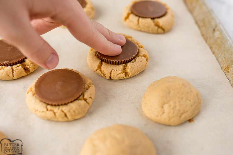 Reese's peanut butter cup being pressed into the baked peanut butter cookie