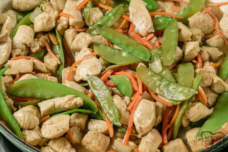 cashew chicken, snow peas and carrots in a pan