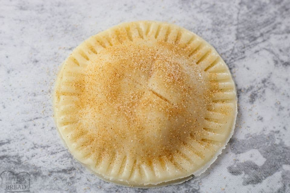 small apple pie with cinnamon sugar on time before baking