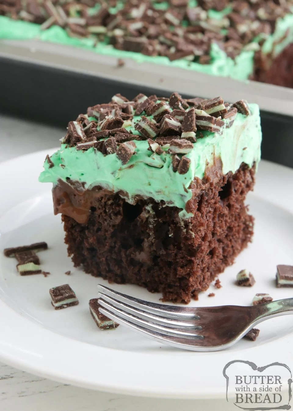 Mint Chocolate Poke Cakemade with acake mix, hot fudge, chocolate pudding and a mint flavored whipped cream topped with chopped Andes mints. Decadent but easy chocolate cake recipe!