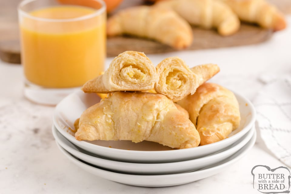Orange Breakfast Crescents made with refrigerated crescent rolls stuffed with a cream cheese filling and topped with a sweet orange frosting! Taste just like orange rolls, but are ready in less than 20 minutes!