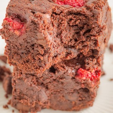 two squares of thick raspberry chocolate brownies stacked with a bite taken out of one