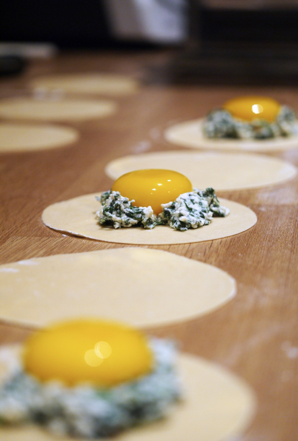 3 homemade ravioli circles with spinach and ricotta rings containing egg yolks