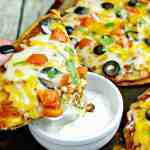 Mexican Pizza slice dipped into sour cream