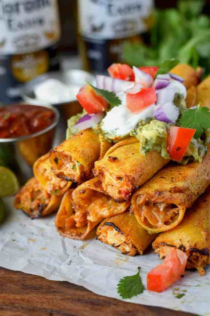 pepper jack chicken taquitos stacked with sour cream, guacamole and pico de gallo on top