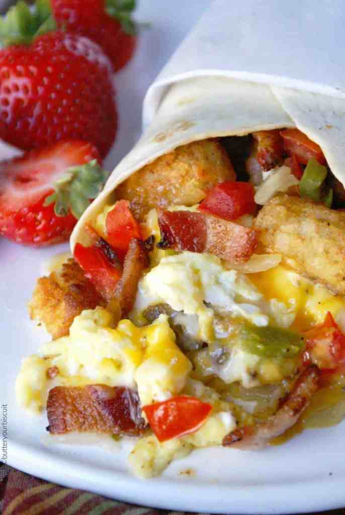 Breakfast Burrito on a white plate with strawberries