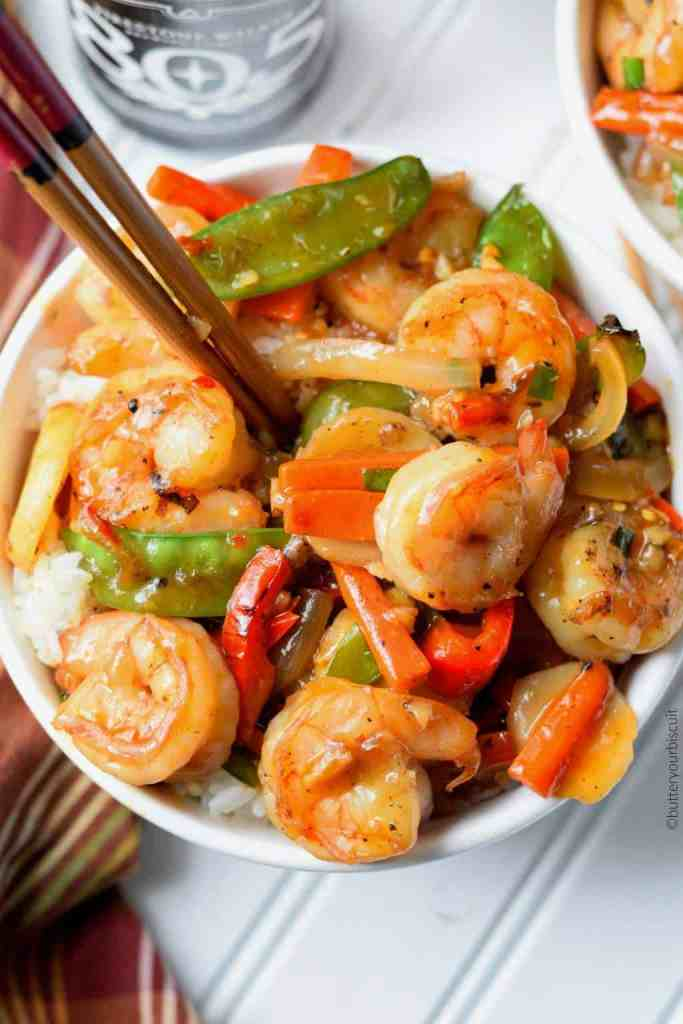 shrimp with hot garlic sauce in a white bowl with chop sticks