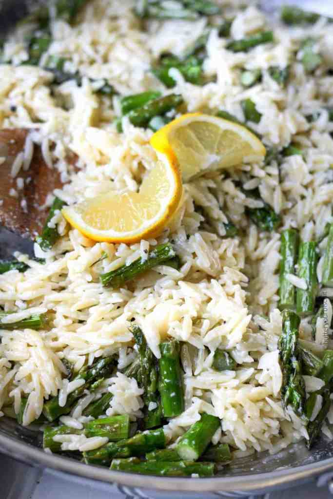 lemon garlic parmesan orzo with roasted asparagus in a pan