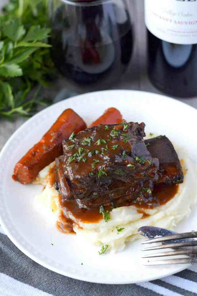 Beef short ribs braised in red wine with carrots on a plate
