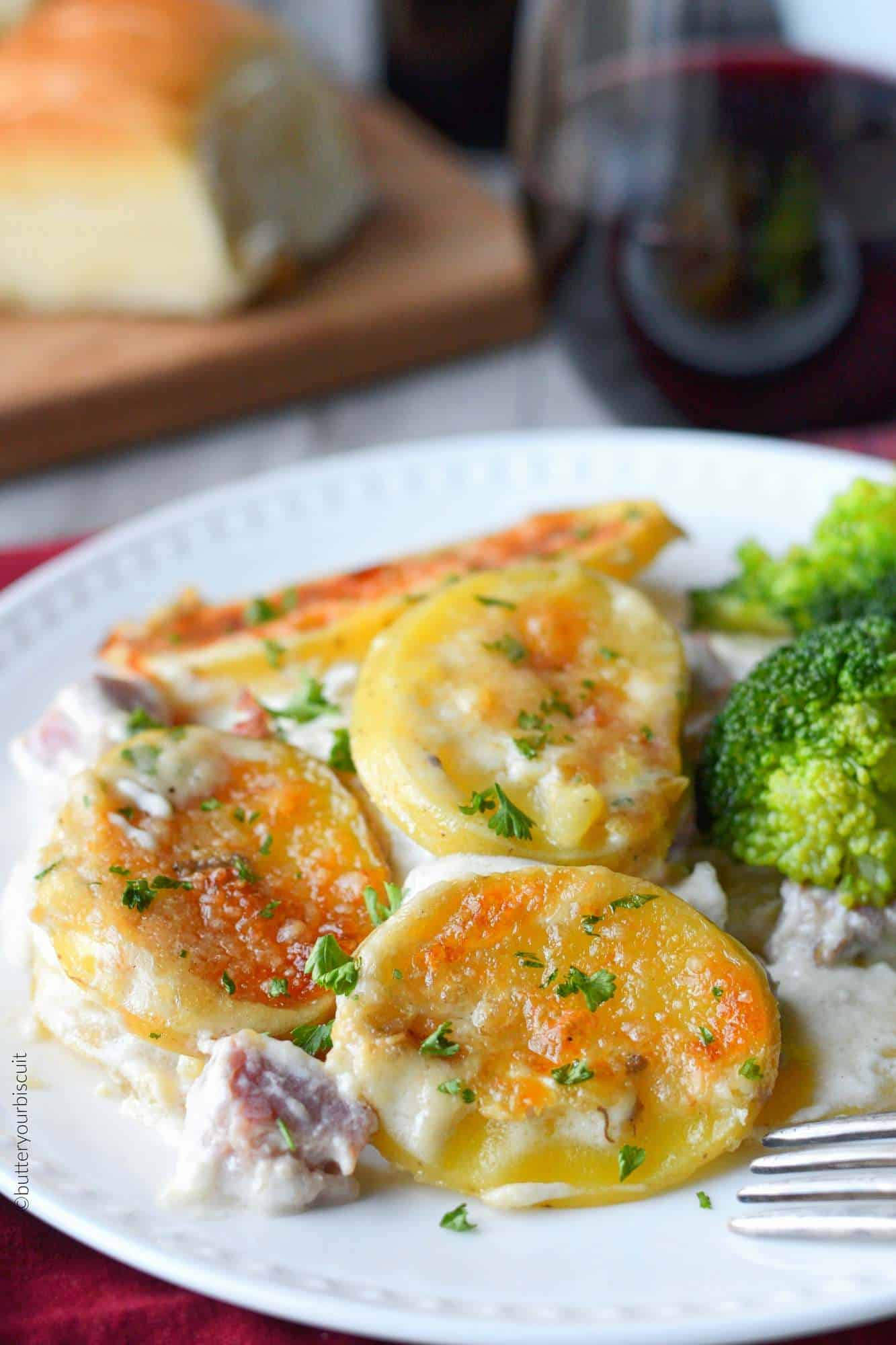 Parmesan Scalloped potatoes and ham on a dinner plate with broccoli