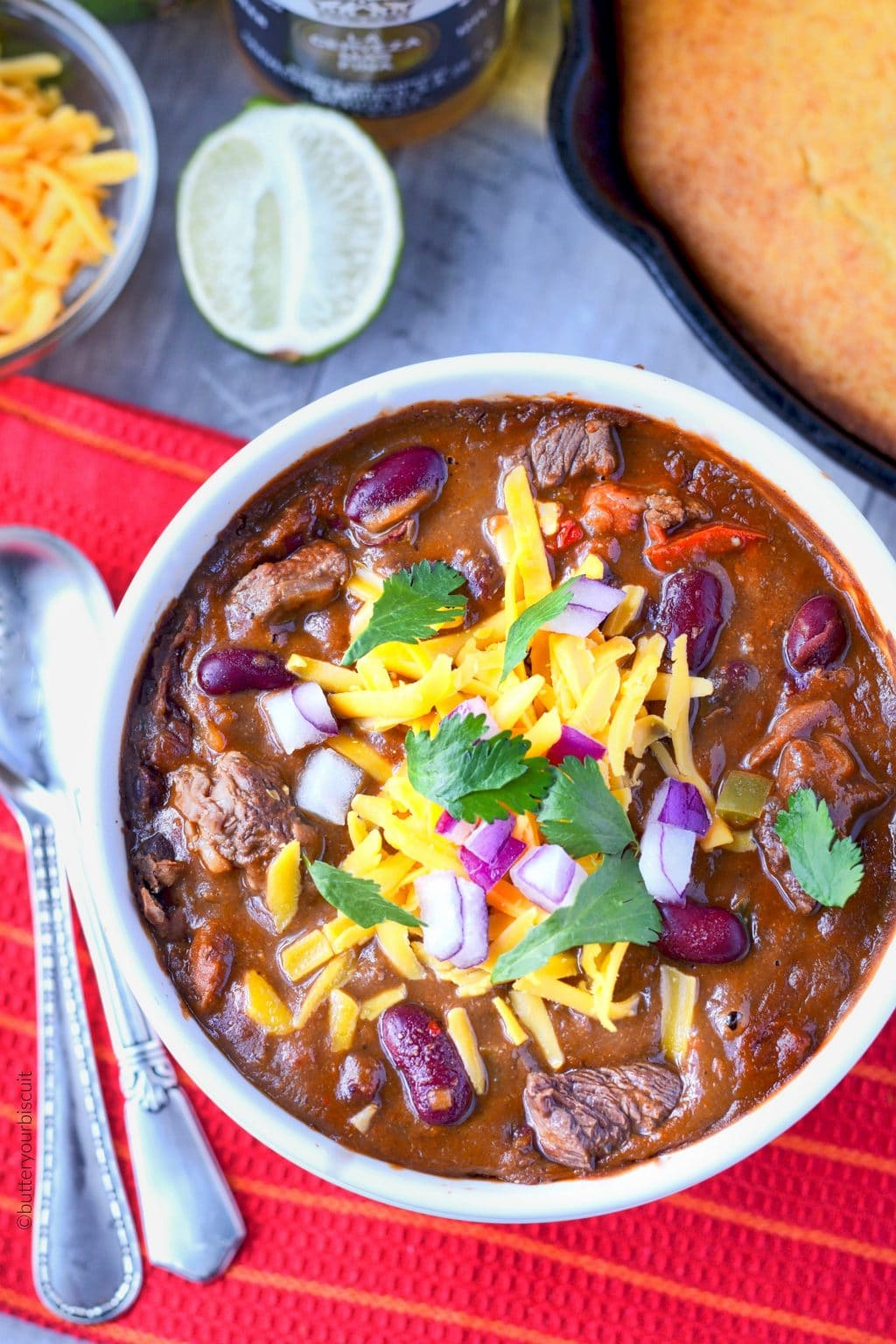 Ribeye steak chili in a white bowl with cornbread