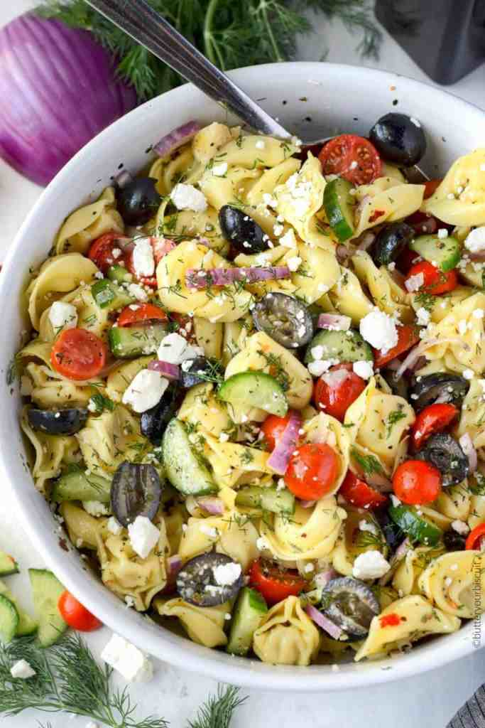 Greek tortellini pasta salad in a large white serving bowl