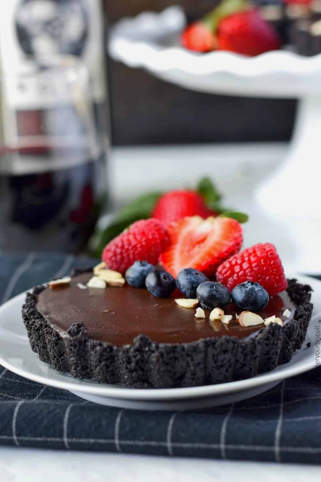 No bake chocolate mini tarts with strawberries, blueberries, rasberries and almond slivers on top on a white plate with a glass of wine
