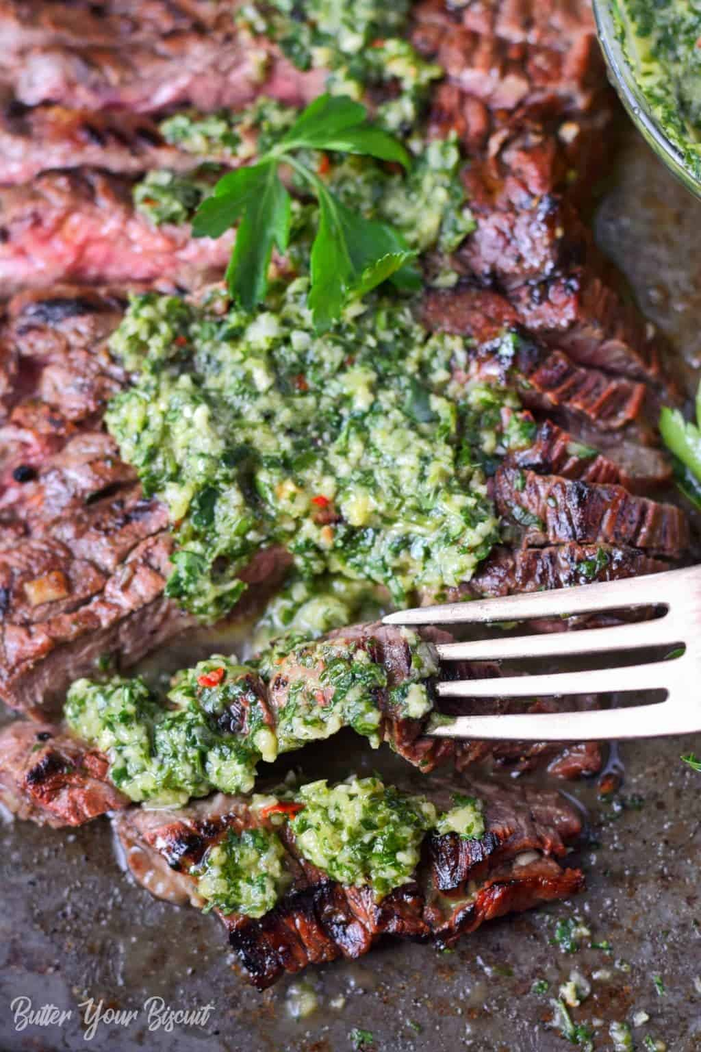Grilled skirt steak and chimichurri on a baking sheet with a fork