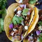slow cooker pork carnitas tacos on a baking sheet with extra cilantro