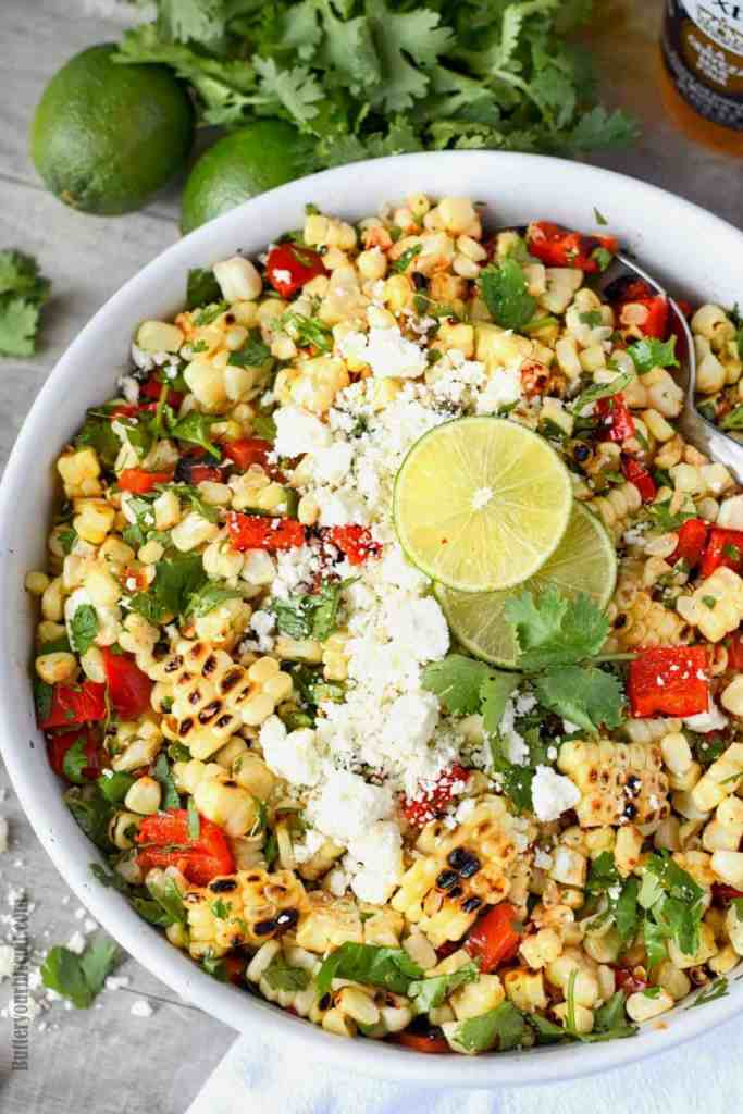 Grilled mexican corn salad in a white bowl with lime slices on top