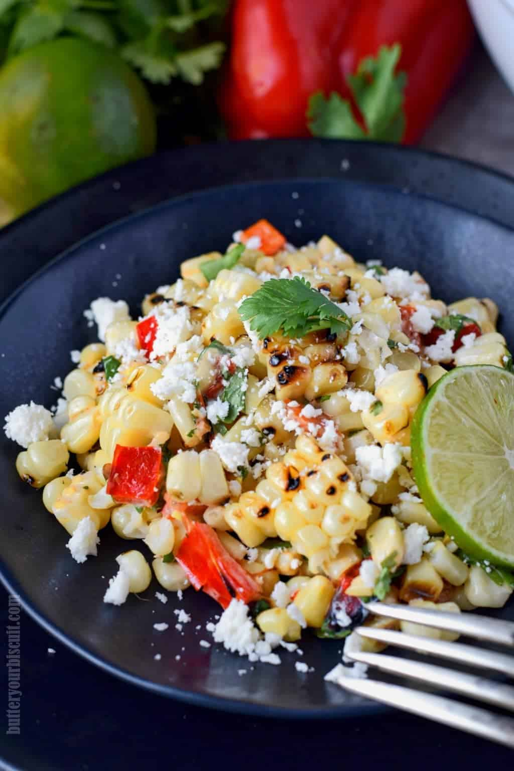 Grilled mexican corn salad on a black plate with limes slices.