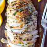Brined herb chicken breasts on a cutting board with lemons and a fork