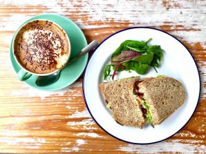 TLT (tofu, lettuce and tomato) sandwich with soya cappucino on a wooden table