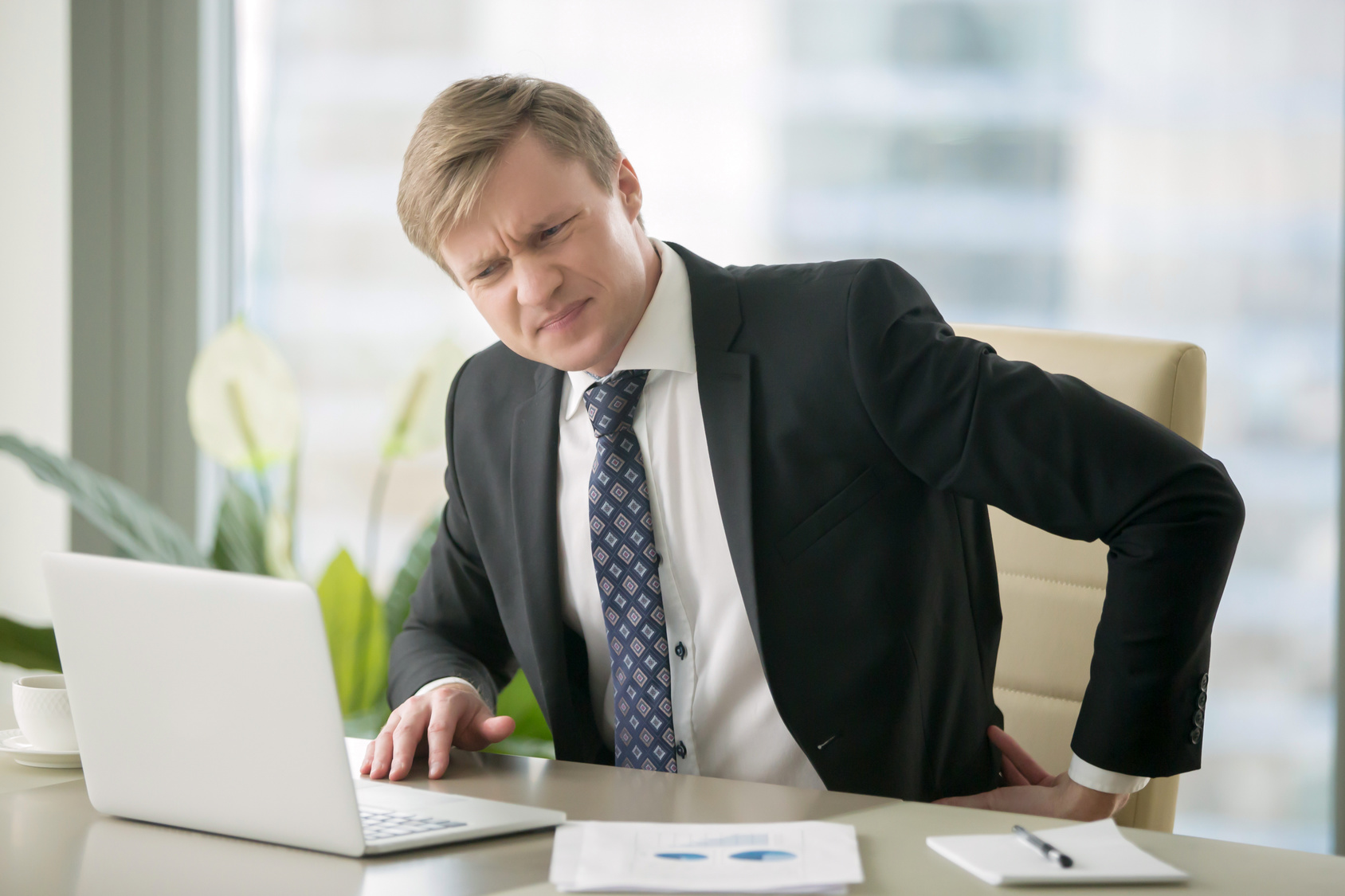 Young businessman holding his back with a pained expression