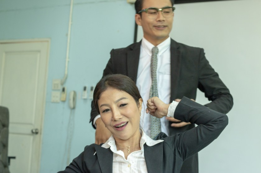 Woman and man stretching to minimize office syndrome