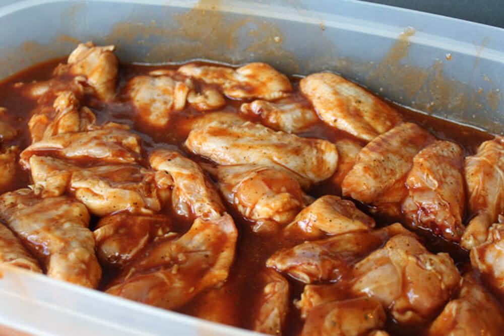 chicken wings marinating in spices, hot sauce and barbecue sauce