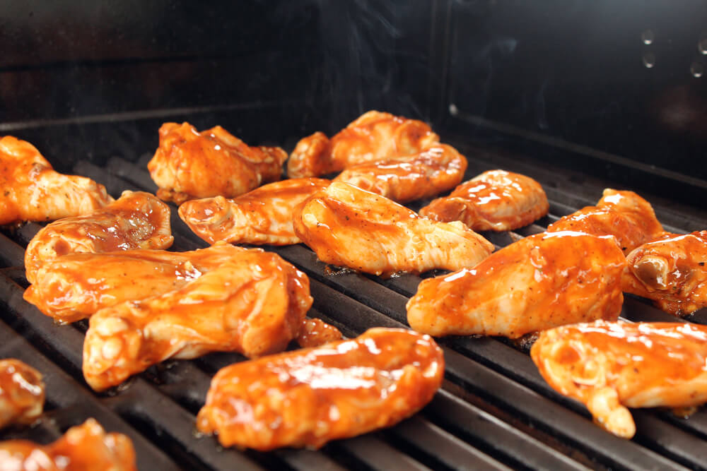 marinated chicken wings on a hot grill