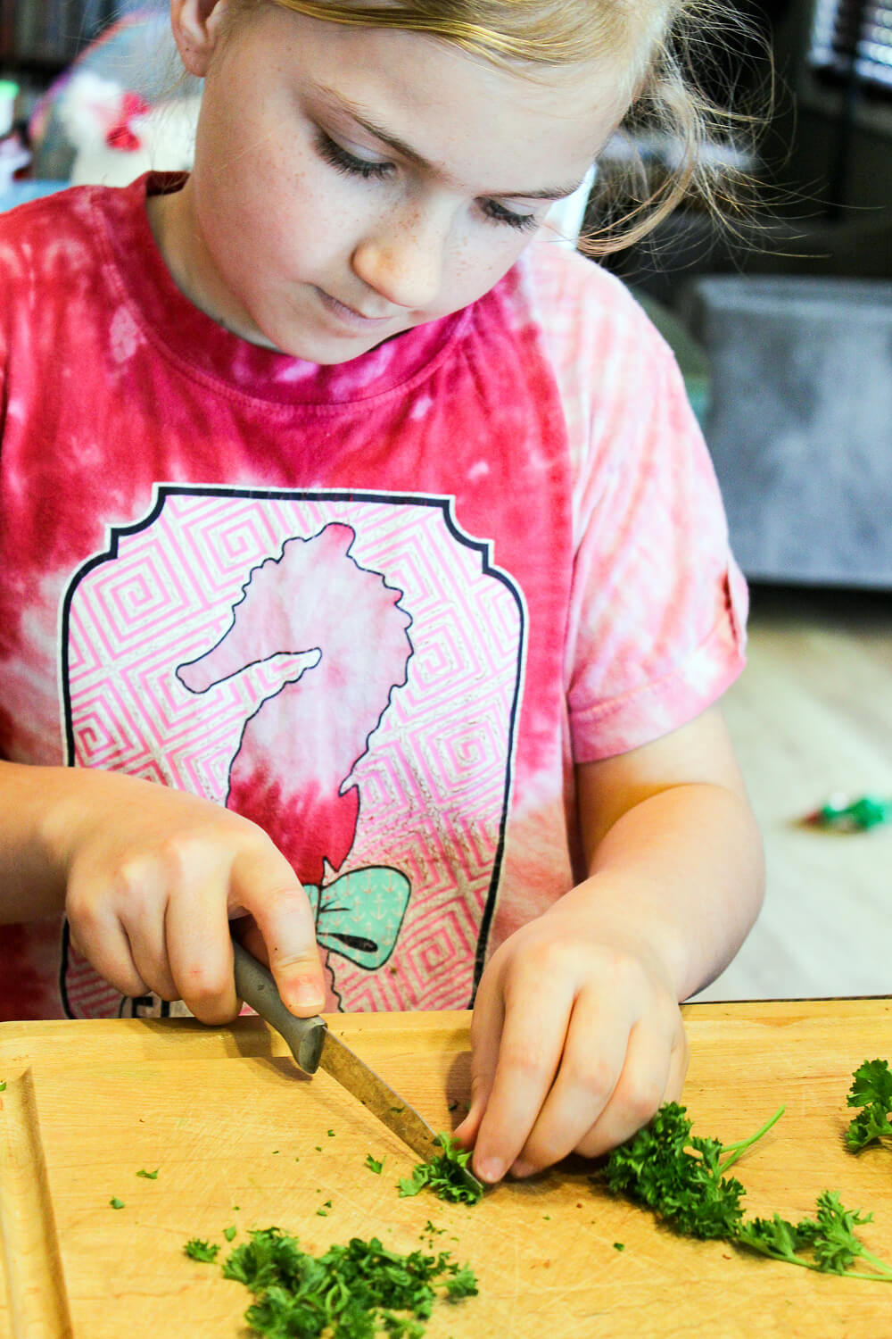 a young girl cutting fresh herbs on a wooden cutting board