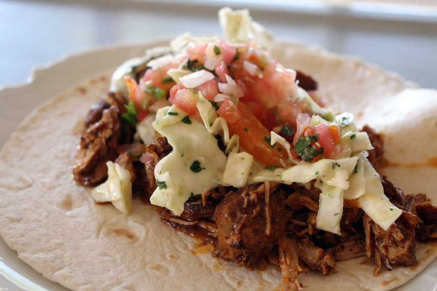 Slow simmered spicy pork loin with homemade refried beans and a fresh sweet cilantro cabbage make our Carnitas Tacos so delicious. Get the recipes here.