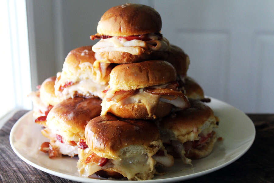 A platter full of stacked slider sandwiches
