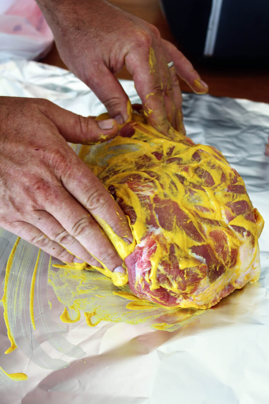 pork butt being rubbed with prepared yellow mustard