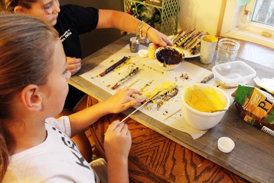 kids making candy coated pretzel sticks