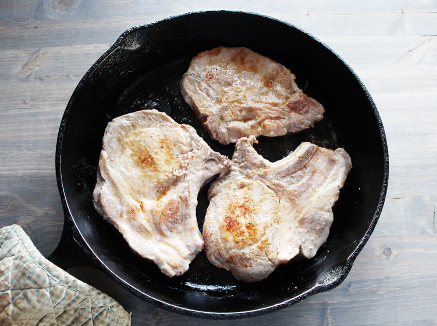 browned pork chops in a skillet