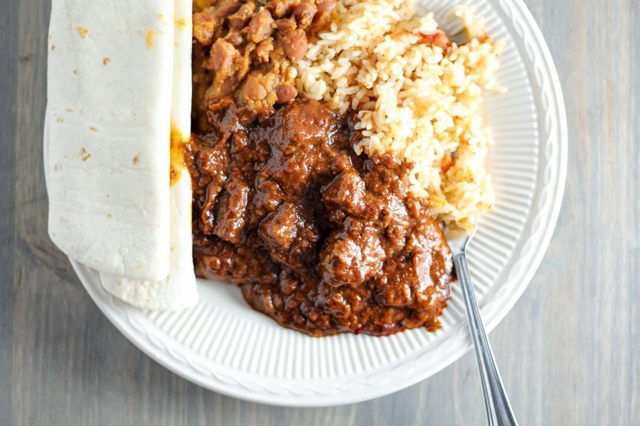 a white plate with Chili Colorado, warm flour tortillas, rice and refried beans