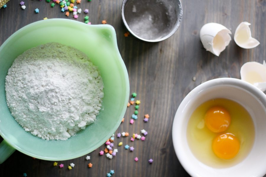 A bowl of cake mix next to a bowl of eggs, on a grey wooden board with funfetti sprinkles