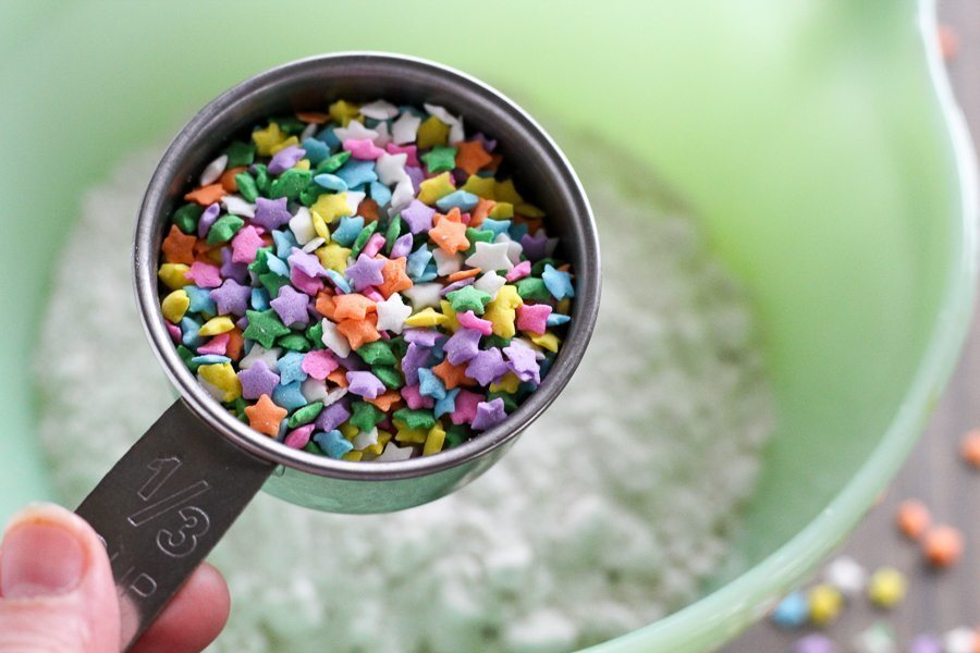A measuring cup full of funfetti sprinkles held over a green bowl of cake waffle batter