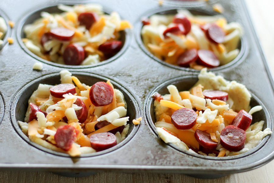 Muffin tin with crescent rolls, each topped with mini pepperoni pieces, sauce and cheese