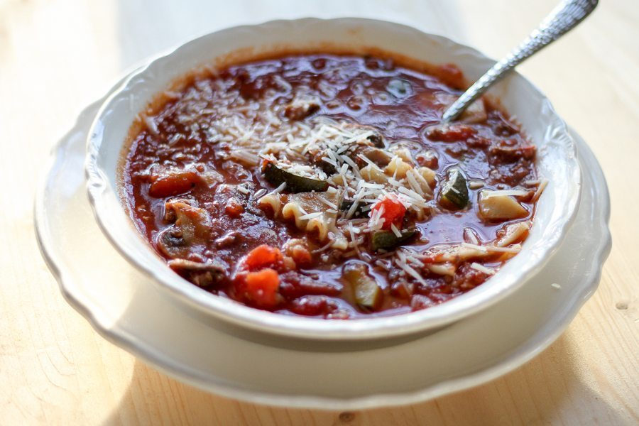 A white bowl on a white platter full of crockpot lasagna soup.